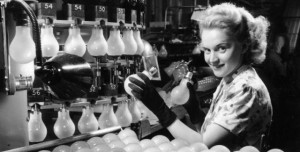Woman in factory working at the light bulb machine