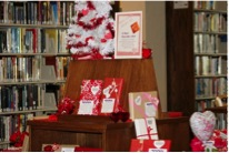 Library room with a display of valentine's day cards and decorations.